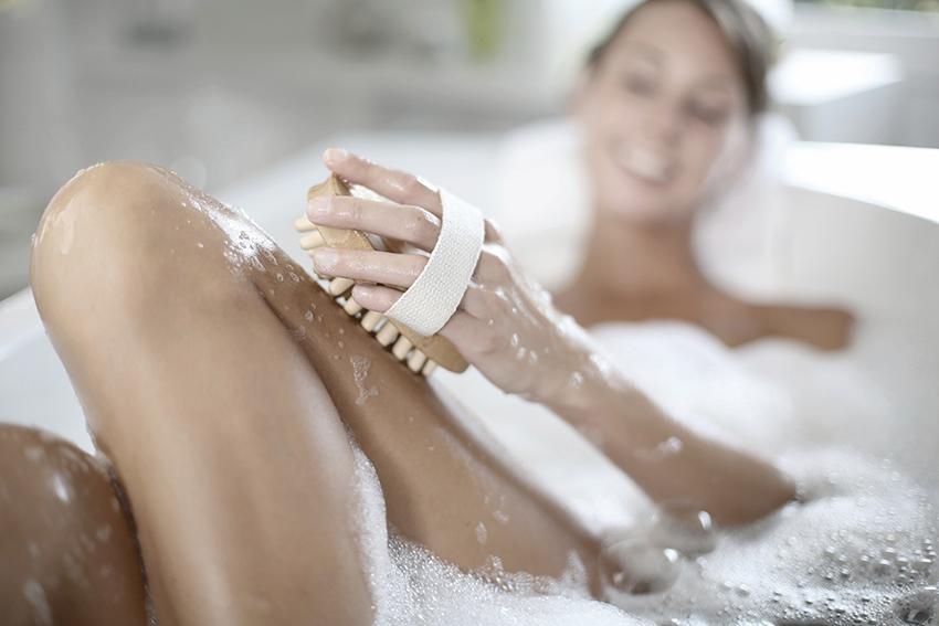 Женщина в ванной делает пилинг